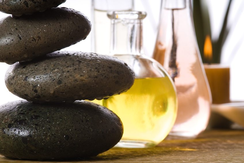 spa products with stones massage flasks and oil